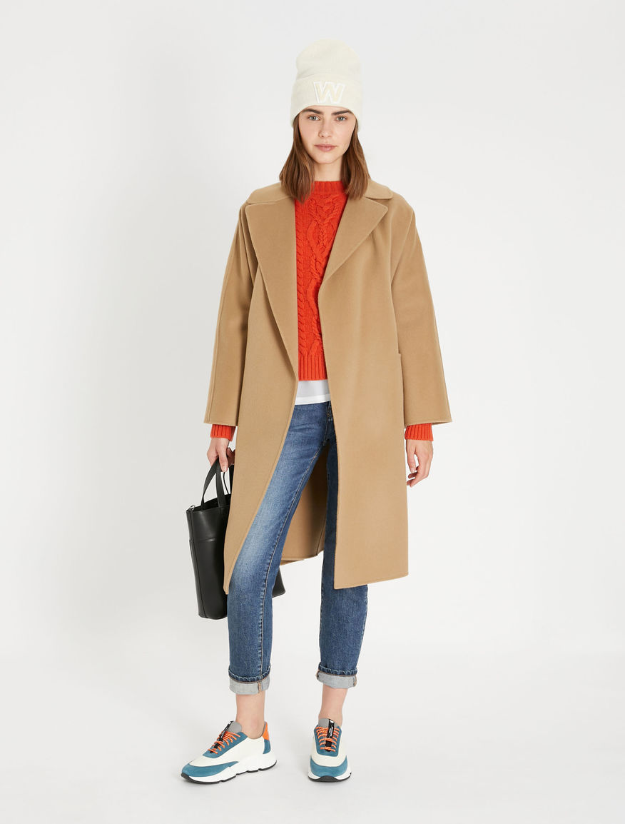 Maxmara weekend camel Rovo coat. Model wears wool camel coat over a red jumper and blue jeans, Autumn 21 trend